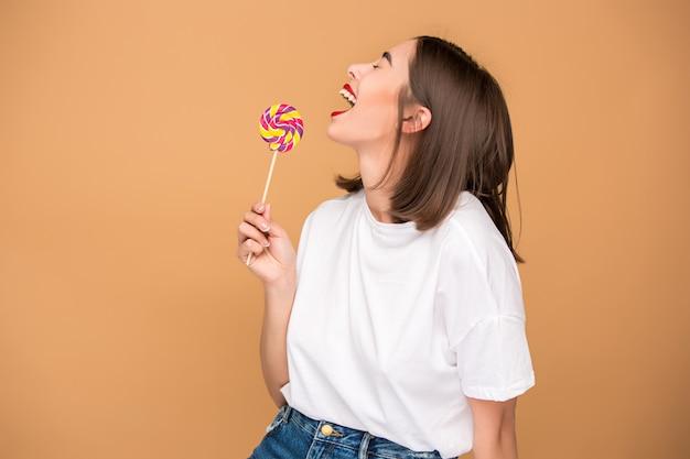 De jonge vrouw met kleurrijke lollipop