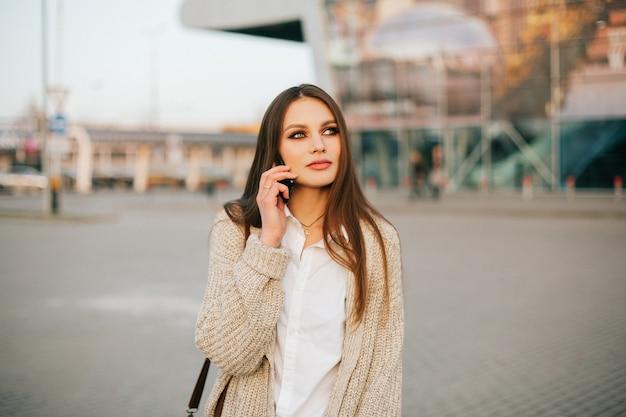 De jonge vrouw met lang haar spreekt op de telefoon lopend buiten in de avond