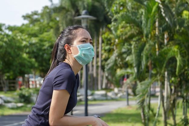 De jonge vrouw met medisch beschermend masker ontspannen in het park. campagne om een beschermend masker te gebruiken tegen covid19