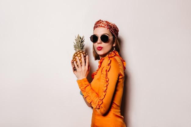 De jonge vrouw met rode lippen houdt ananas. portret van ondeugend meisje in oranje outfit en zonnebril op witte ruimte.