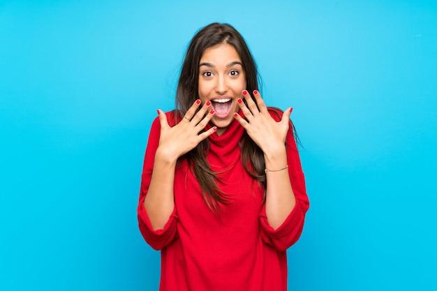 De jonge vrouw met rode sweater isoleerde blauw met verrassingsgelaatsuitdrukking