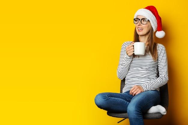 De jonge vrouw met verbaasd gezicht in santahoed zit op een stoel en houdt een kop