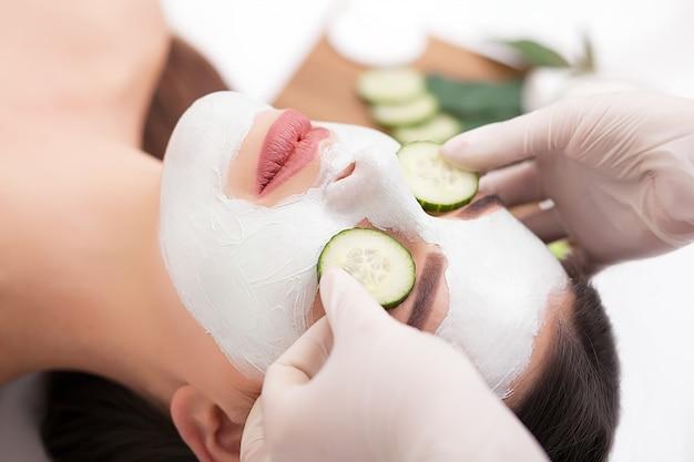 De jonge vrouw met voedingsstoffen gezichtsmasker in schoonheidssalon, sluit omhoog