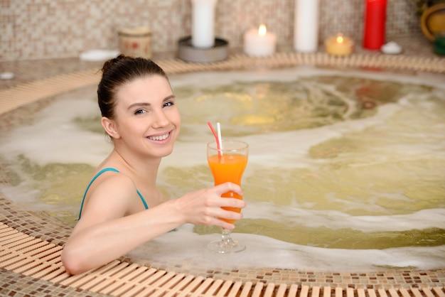 De jonge vrouw neemt schuimbad met kaars.