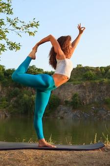 De jonge vrouw oefent yoga dichtbij rivier uit