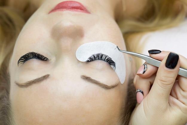 De jonge vrouw ondergaat een procedure voor de verlenging van de close-upwimper. wimperborstel Premium Foto