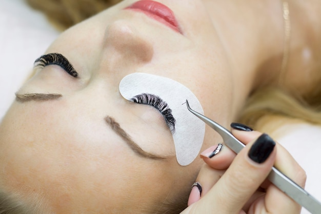De jonge vrouw ondergaat een procedure voor de verlenging van de close-upwimper. wimperborstel