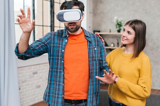 De jonge vrouw ondersteunend de man die virtuele werkelijkheidscamera dragen wat betreft van hem dient de lucht in