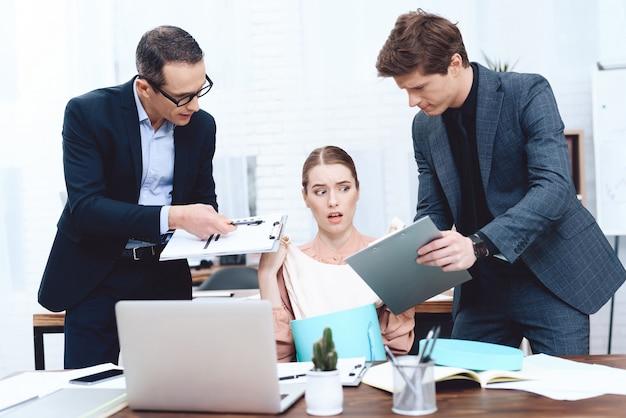 De jonge vrouw ontspant op het werk. leiders klagen erover.