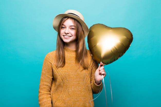 De jonge vrouw ontvangt lucht baloon op verjaardagsviering die over kleurenmuur wordt geïsoleerd
