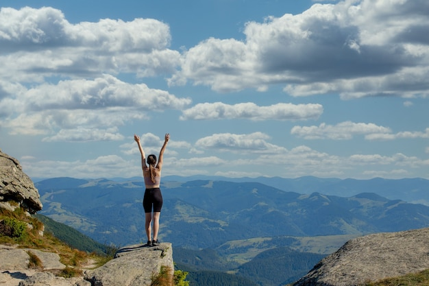 De jonge vrouw op de top van de berg hief haar handen op naar de blauwe lucht