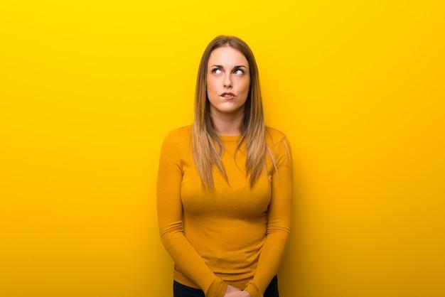 De jonge vrouw op gele achtergrond met verwart gezichtsuitdrukking terwijl bijtlip