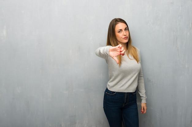 De jonge vrouw op geweven muur die duim toont ondertekent neer met negatieve uitdrukking