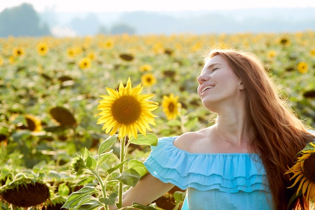 De jonge vrouw op zonnebloemgebied heeft pret
