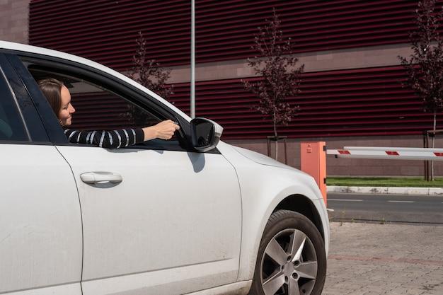 De jonge vrouw opent een slagboom door middel van de afstandsbediening van de salon van een auto