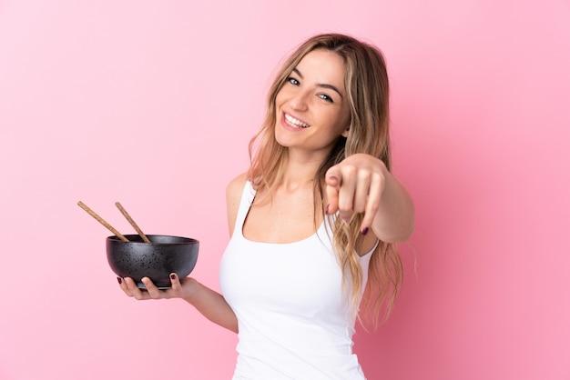 De jonge vrouw over geïsoleerde roze muur richt vinger op u met een zekere uitdrukking terwijl het houden van een kom van noedels met eetstokjes