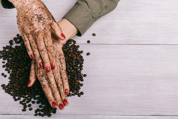 De jonge vrouw past een koffiescrub op handen toe
