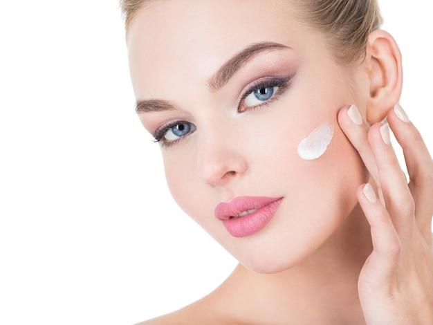 De jonge vrouw past kosmetische room toe op een gezicht.