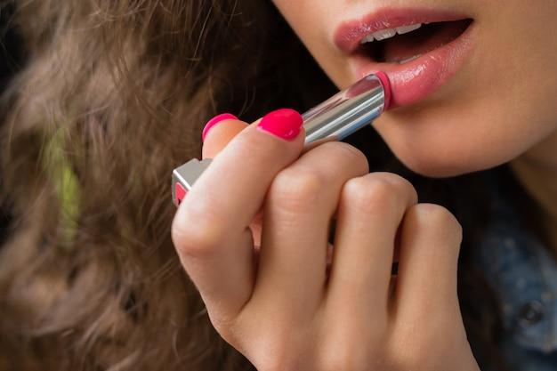 De jonge vrouw past lippenstiftclose-up toe