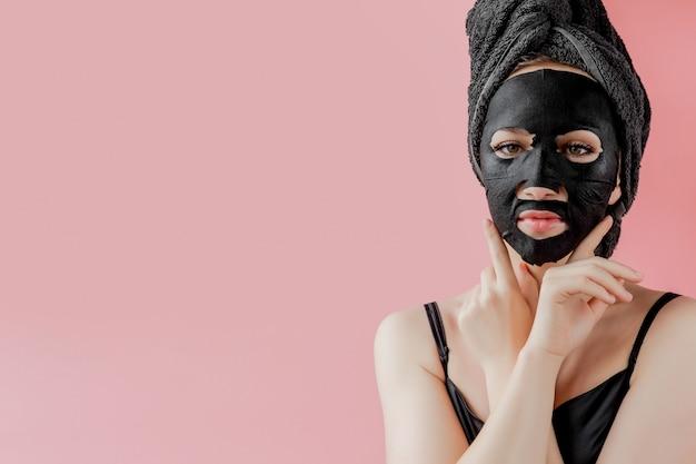 De jonge vrouw past zwart kosmetisch stoffen gezichtsmasker op roze achtergrond toe. gezichtspeeling masker met houtskool, spa schoonheidsbehandeling, huidverzorging, cosmetologie. detailopname