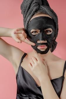 De jonge vrouw past zwart kosmetisch stoffen gezichtsmasker op roze muur toe. gezichtspeeling masker met houtskool, spa schoonheidsbehandeling, huidverzorging, cosmetologie. detailopname
