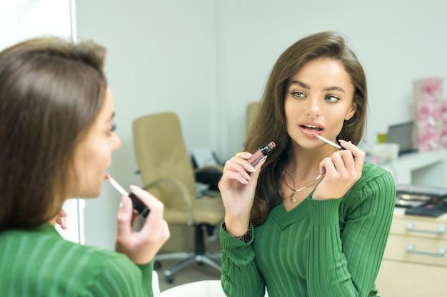 De jonge vrouw schildert lippen in beige