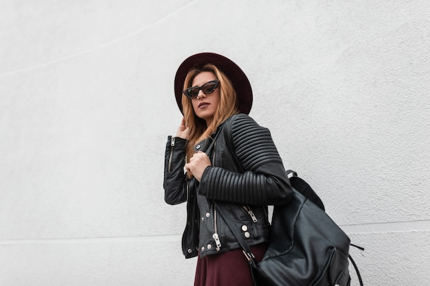 De jonge vrouw sexy stedelijke hipster in een modieuze hoed in stijlvolle zonnebril in een vintage leren jas met een rugzak