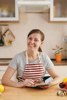 De jonge vrouw snijdt groenten in de keuken met een mes en laptop op tafel. groentesalade. dieetconcept. gezonde levensstijl. thuis koken. eten koken.