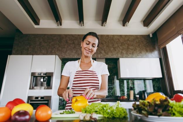 De jonge vrouw snijdt groenten in de keuken met een mes