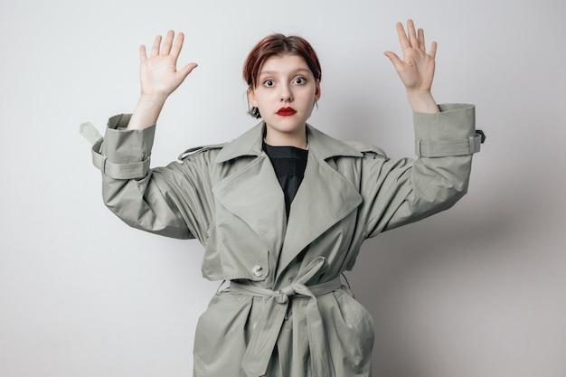 De jonge vrouw stak haar handen op, geeft zich over