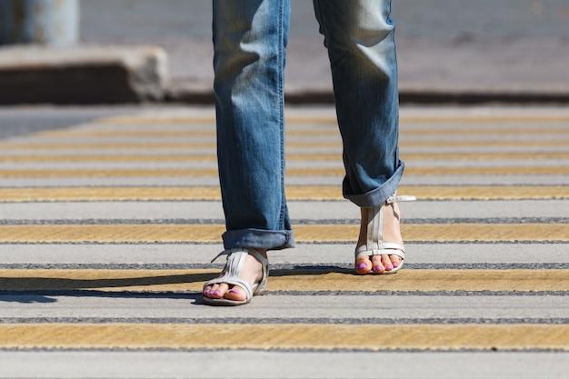 De jonge vrouw steekt de straat over bij een zebrapad