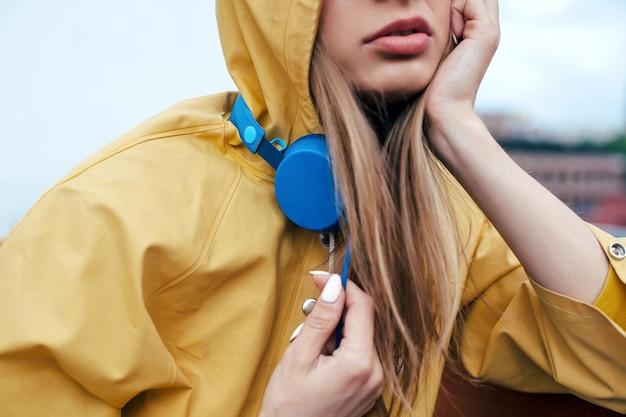 De jonge vrouw stelt openlucht met blauwe modieuze oortelefoons gekleed in gele regenjas. closeup portret