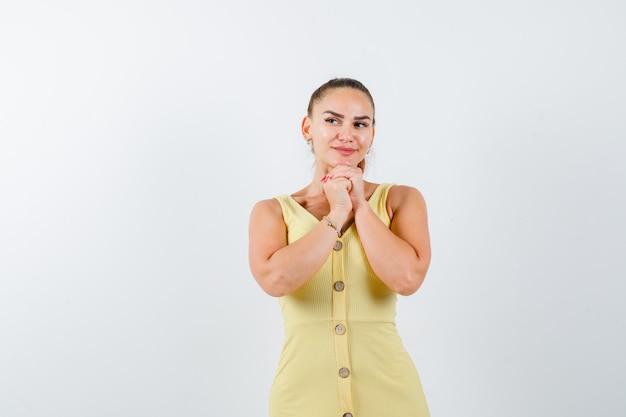 De jonge vrouw steunt kin op gevouwen handen in gele kleding en kijkt dromerig, vooraanzicht.