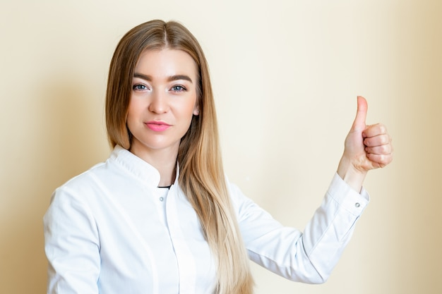 De jonge vrouw toont duimen.