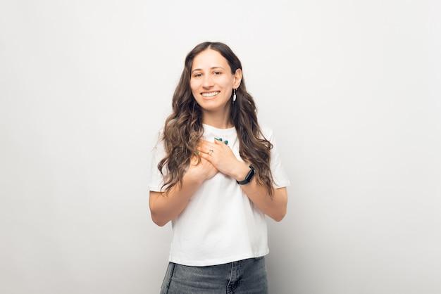 De jonge vrouw toont medeleven. gebaren met handen over de borst.