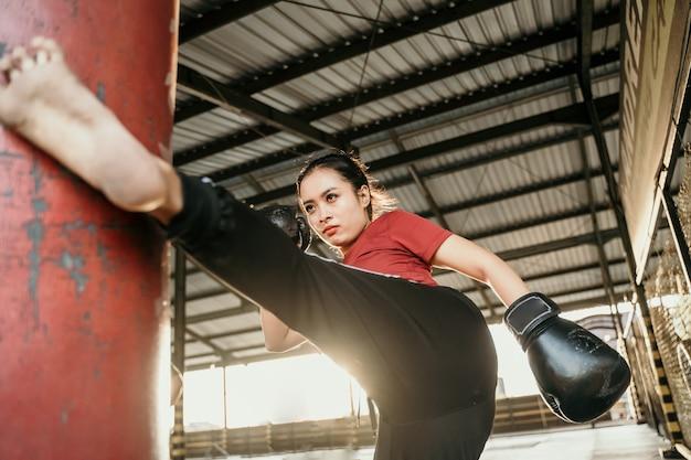 De jonge vrouw traint een schop op de bokszak in de sportschool