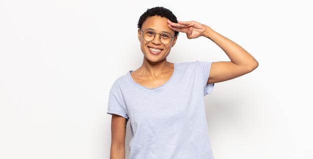 De jonge vrouw van afro begroet het front met een militaire groet in een daad van eer en patriottisme en toont respect