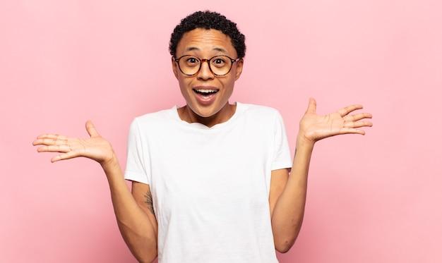 De jonge vrouw van afro voelt zich blij, opgewonden, verrast of geschokt, glimlacht en verbaasd over iets ongelooflijks