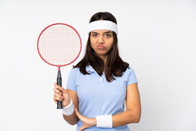 De jonge vrouw van de badmintonspeler over geïsoleerde witte muur die verstoord voelen