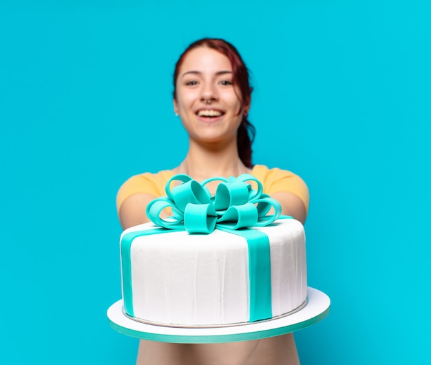 De jonge vrouw van de bakkerijwerknemer met een verjaardagstaart