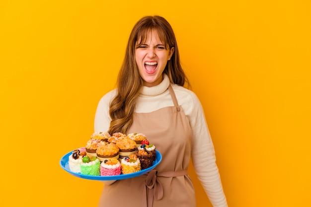 De jonge vrouw van de banketbakker die op gele muur wordt geïsoleerd die zeer boos en agressief gillen