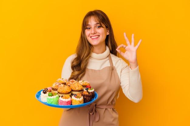 De jonge vrouw van de banketbakker op geel vrolijk en zeker tonend ok gebaar.