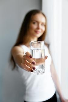 De jonge vrouw van de close-up toont glas water