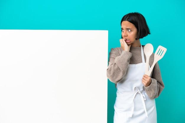 De jonge vrouw van de gemengd raskok met een groot aanplakbiljet dat op blauwe achtergrond zenuwachtig en bang wordt geïsoleerd
