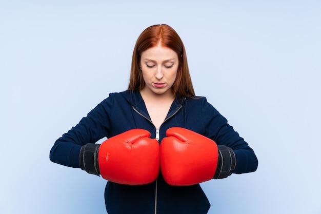 De jonge vrouw van de roodharigesport over geïsoleerd blauw met bokshandschoenen