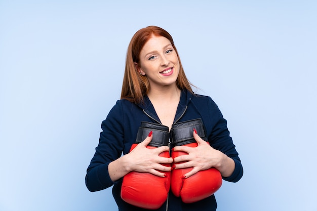 De jonge vrouw van de roodharigesport over geïsoleerde blauwe muur met bokshandschoenen