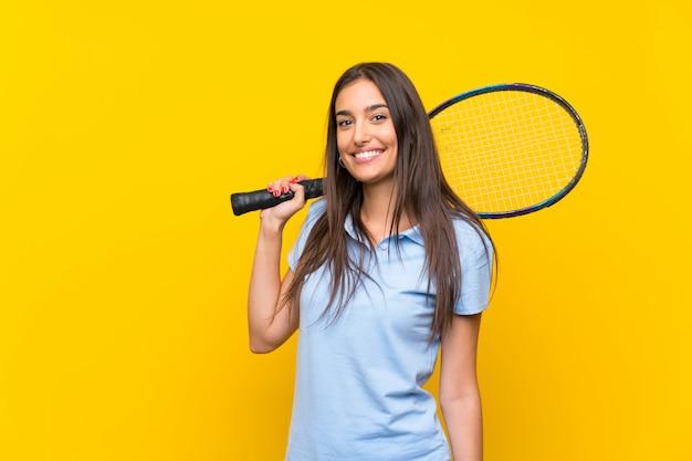 De jonge vrouw van de tennisspeler over geïsoleerde gele muur