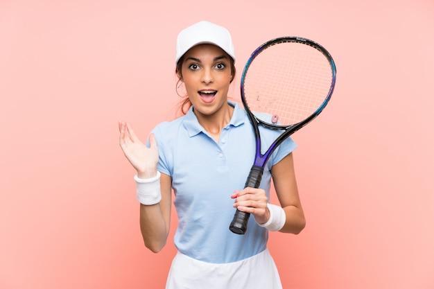 De jonge vrouw van de tennisspeler over geïsoleerde roze muur met geschokte gelaatsuitdrukking