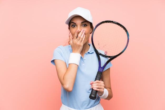 De jonge vrouw van de tennisspeler over geïsoleerde roze muur met verrassingsgelaatsuitdrukking