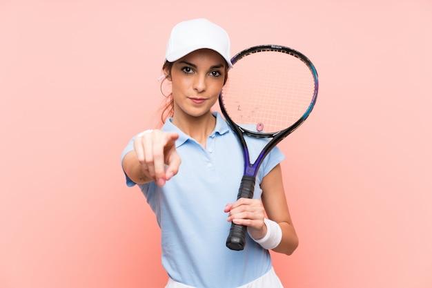 De jonge vrouw van de tennisspeler over geïsoleerde roze muur richt vinger op u met een zekere uitdrukking